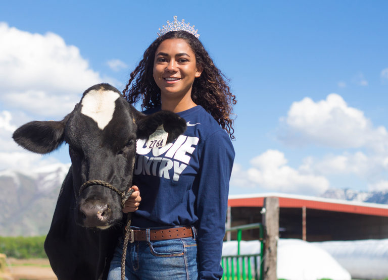 Alexis Cooper Miss USU with a cow