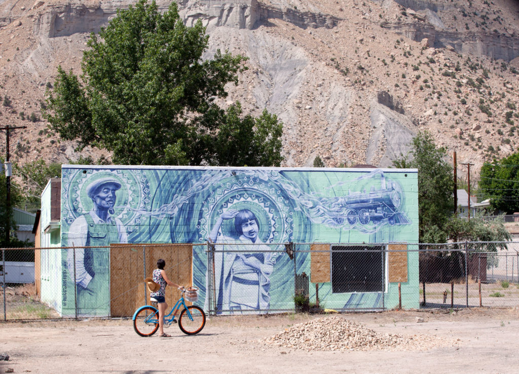 Cyclist in front of a mural where her husband's family history is on display.
