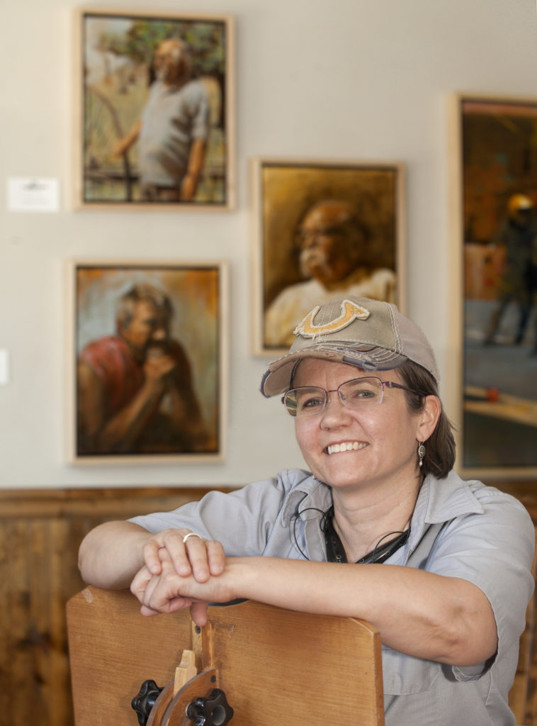 Photo of painter Kate Kilpatrick Miller in front of some of her paintings.