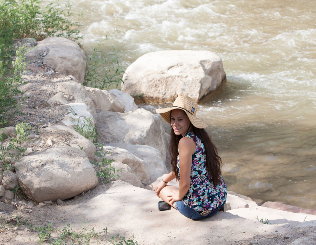 Malarie Matsuda sitting on rocks by the Price River.