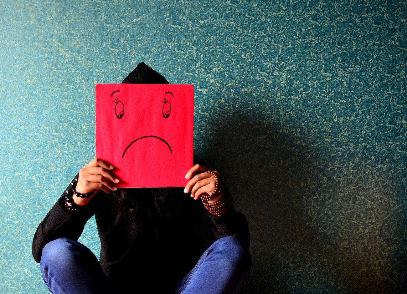 man sitting on wall holding a sad face sign