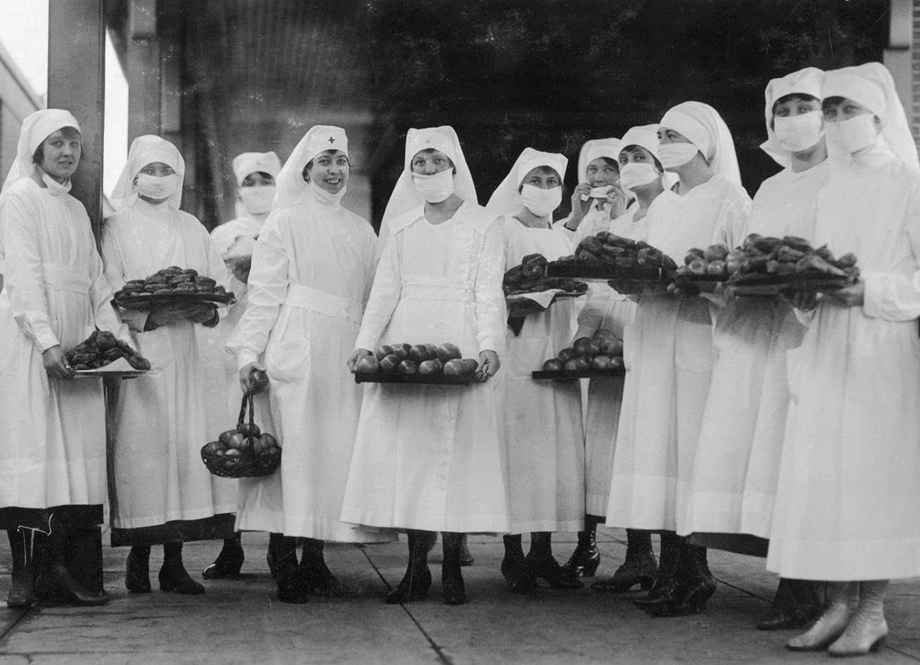 WWI nurses wear masks and hold plates of food for the sick.
