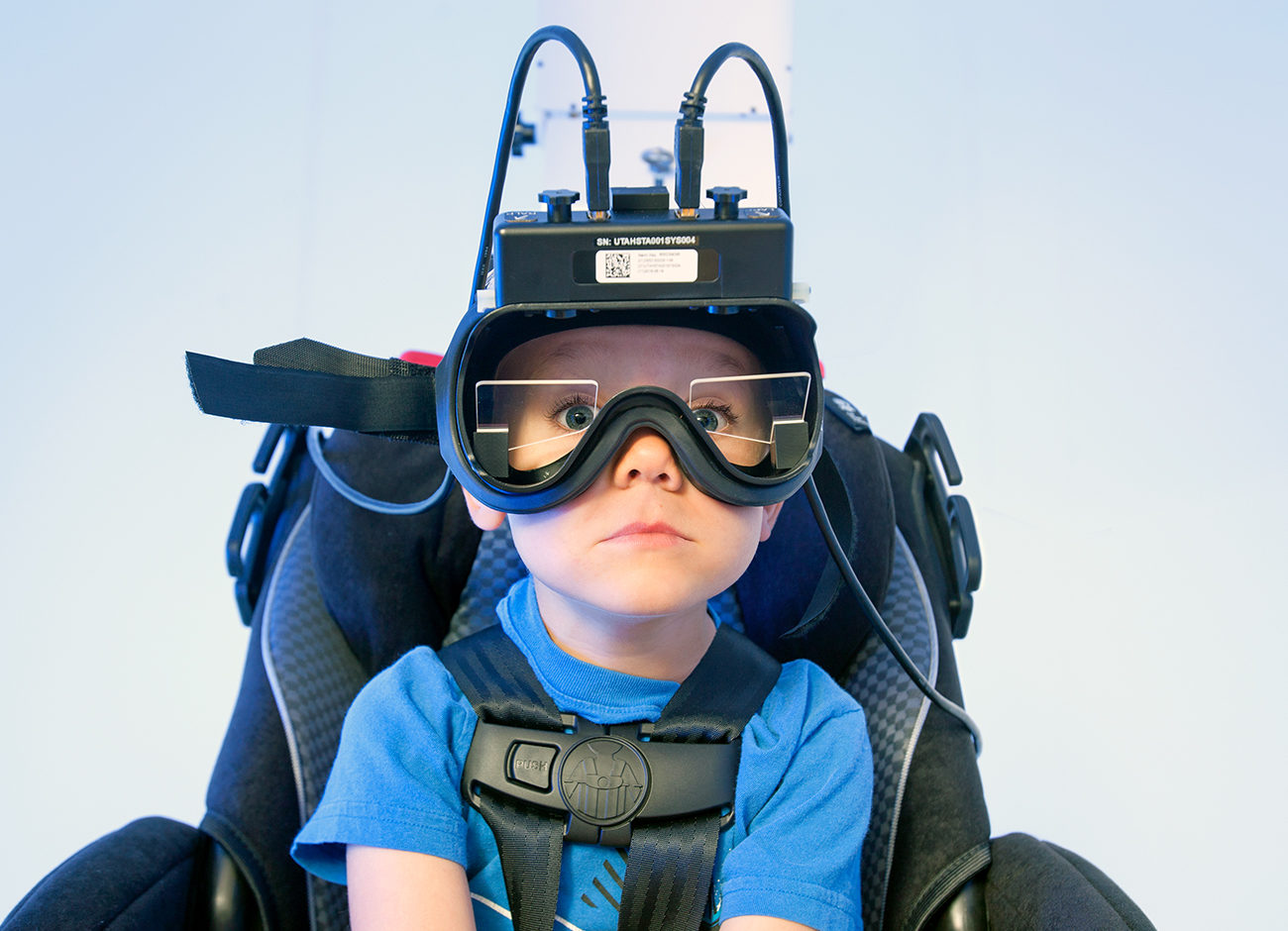 A little boy sits in the vestibular chair awaiting testing.