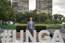 Man standing next to the UNGA sign in New York