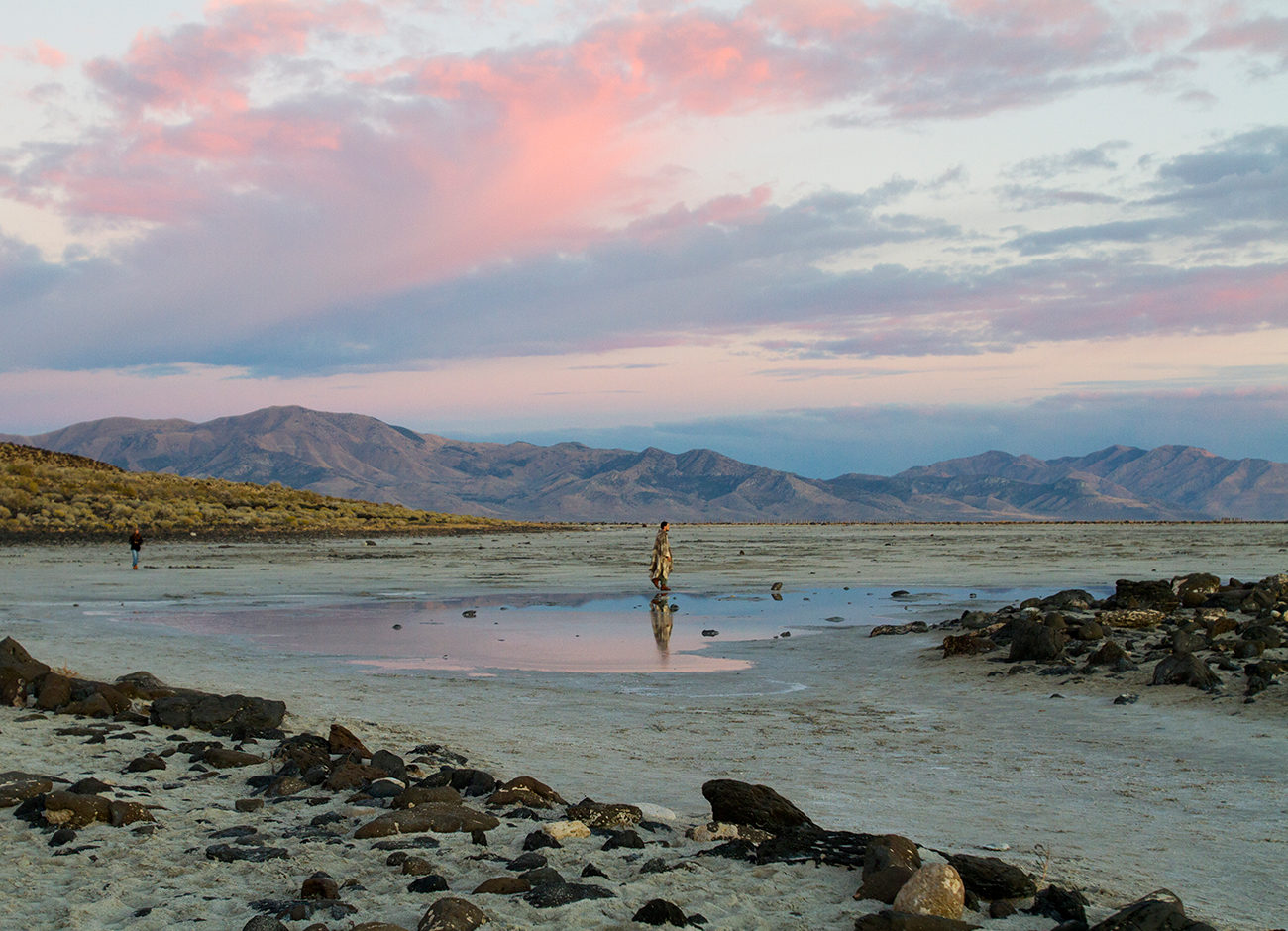 A man walks on the dry lakebed of the Great Salt Lake at sunset.