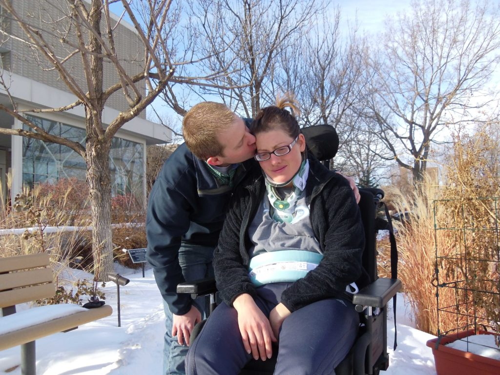 Chauncy and Kelli outside in the snow after the accident. Kelli sits in a wheelchair while Chauncy kisses her head.