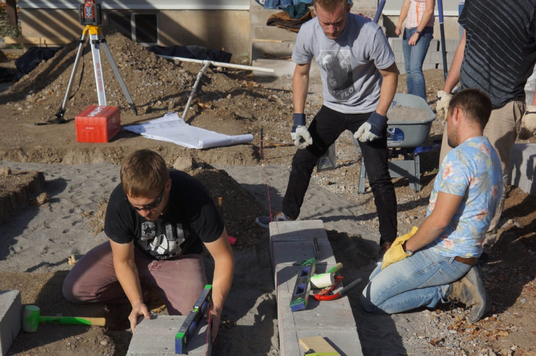 Students work on the cement base for a project