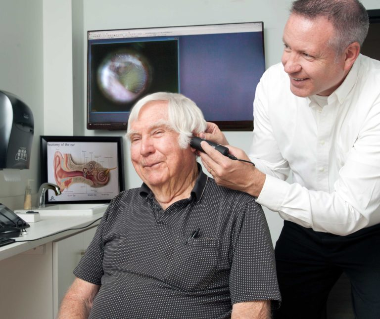 A senior citizen has his ears checked by an audiologist at the Sorenson Center.