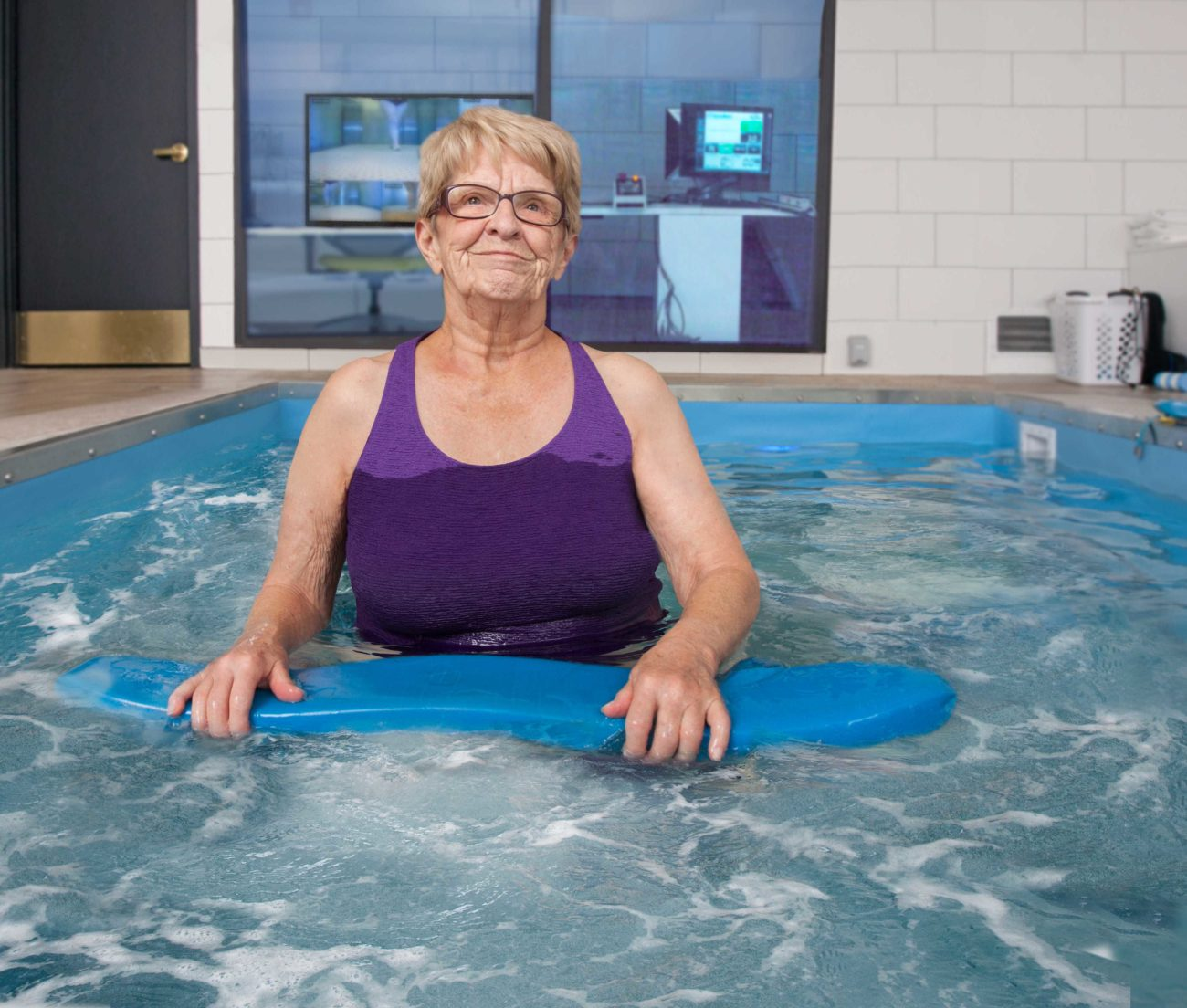 a woman stands in the hydropool for a therapy session.