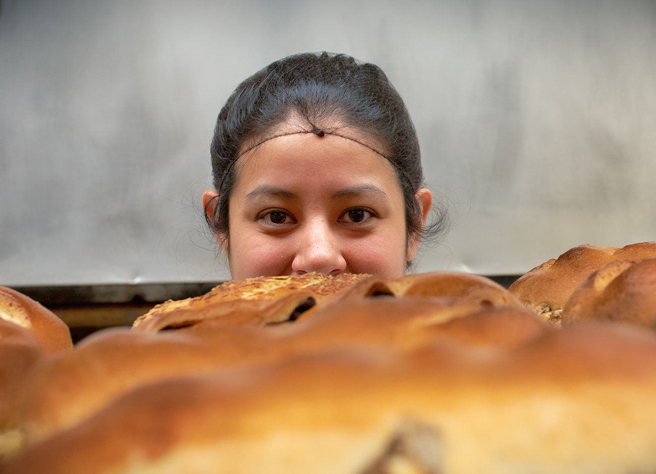 A face peeking from behind bread
