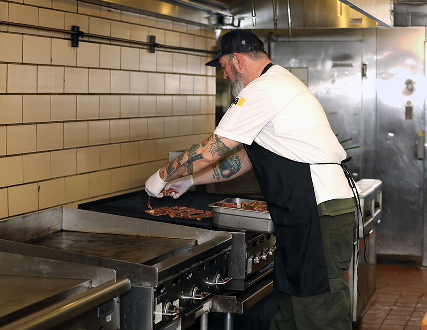 Chef Don Donaldson cooking at the Junction. The tattoos of a chef's knife, onion, and garlic are visible on his left arm.