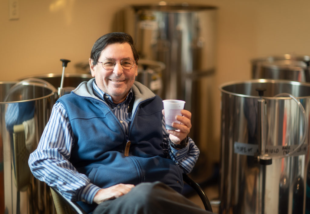 Mark Bold holding a plastic cup containing one of his 10 varieties of wine.