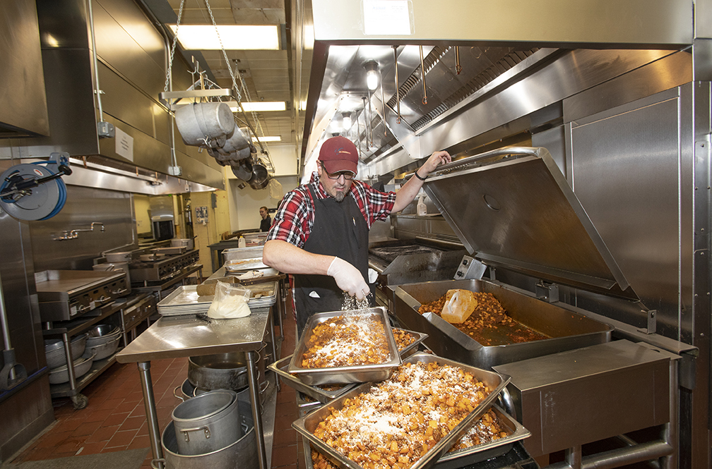 Executive Cheff Jeff Woolley seasons trays of potatoes.