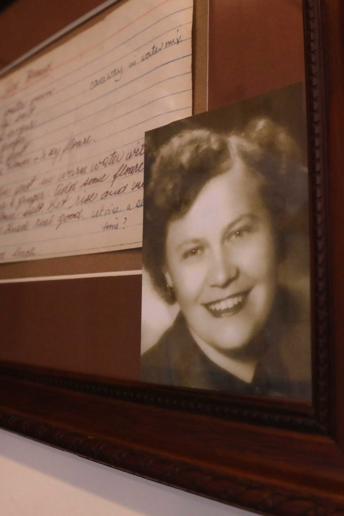 A framed black and white photo of woman and handwritten recipe for rye bread on a wall.