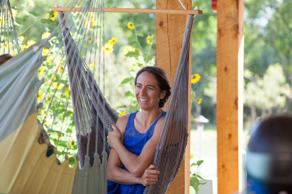 woman sits in hammock smiling