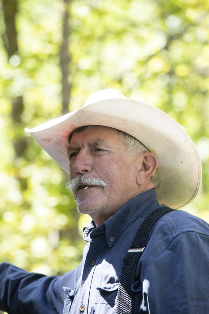rancher talks with a toothpick in his teeth and white cowboy hat shading his face.