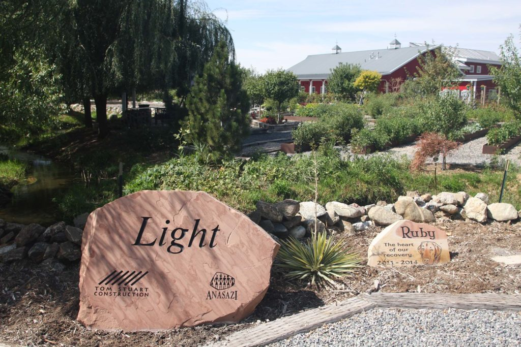 "A rock with the word ""light"" carved into it sits in front of a red barn"