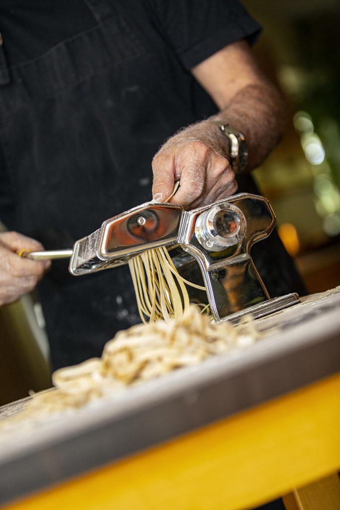 Hands feeding pasta through a pasta machine.
