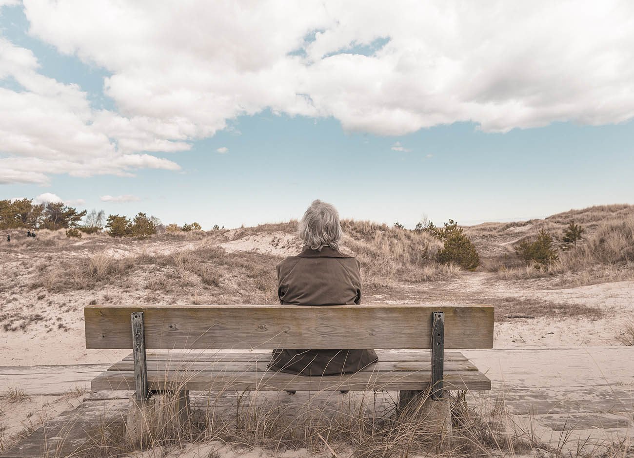 older woman sitting on a bench looking at the sky