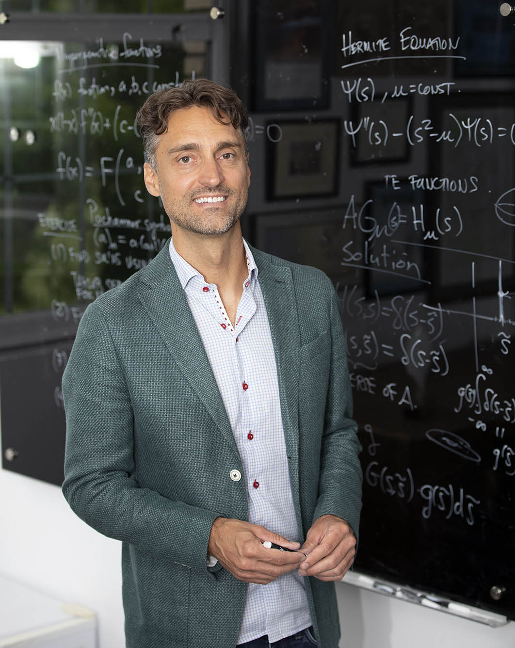 nathan geer stands in front of a blackboard with mathematical equations scrawled on it