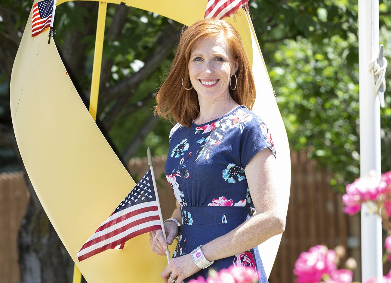 Jennie Taylor stands in her backyard holding an American flag.