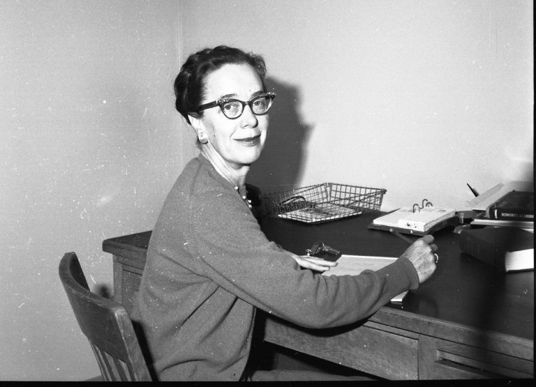 A kind looking woman smiles into the camera while sitting at her desk