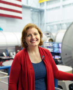 A woman stands in front of a mockup of the International Space Station at the Johnson Space Center in Houston.