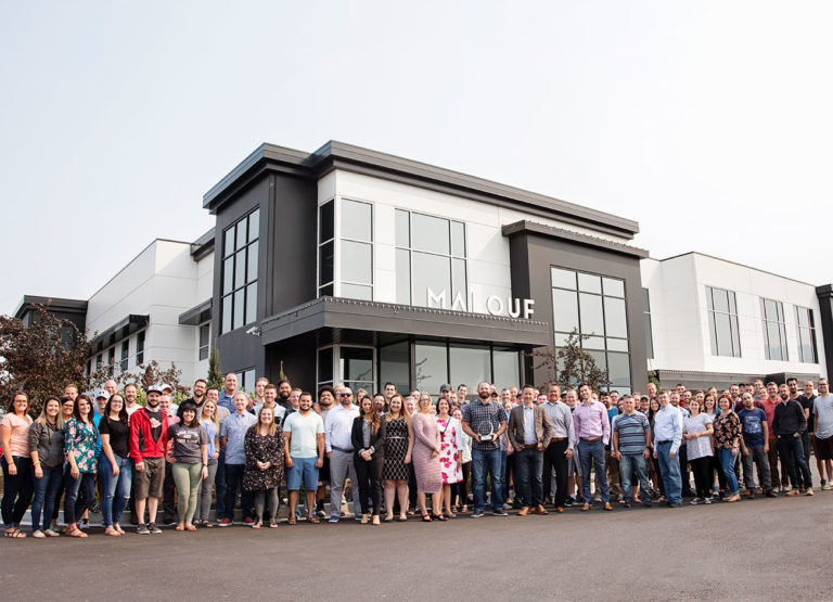 Malouf founders and the Logan-based employees stand outside the company's massive building in Nibley.