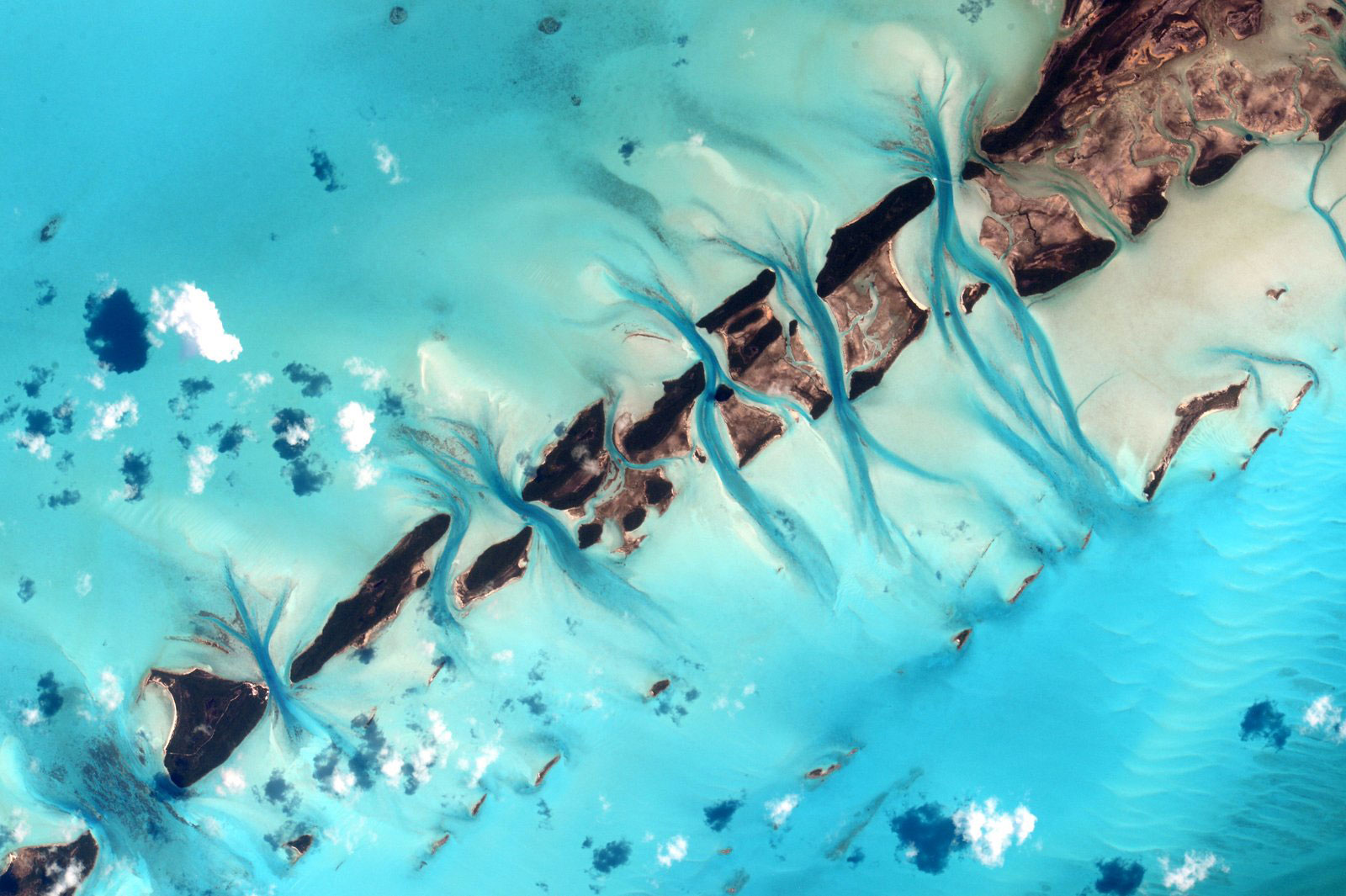 Aqua waters stream between the islands of the Bahamas - aerial art viewed from space.