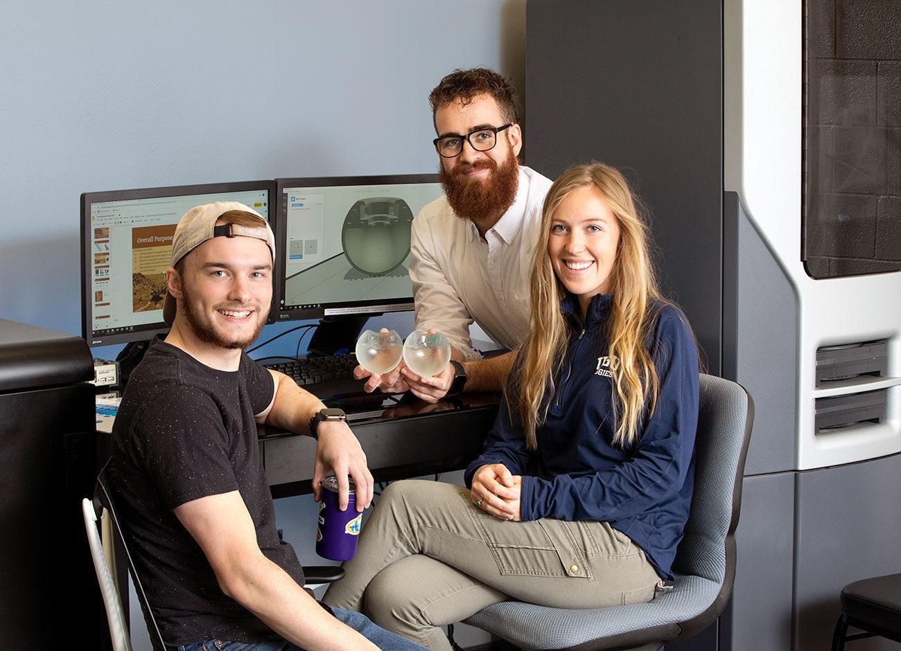 three students display their handheld device to help NASA detect life on Mars.