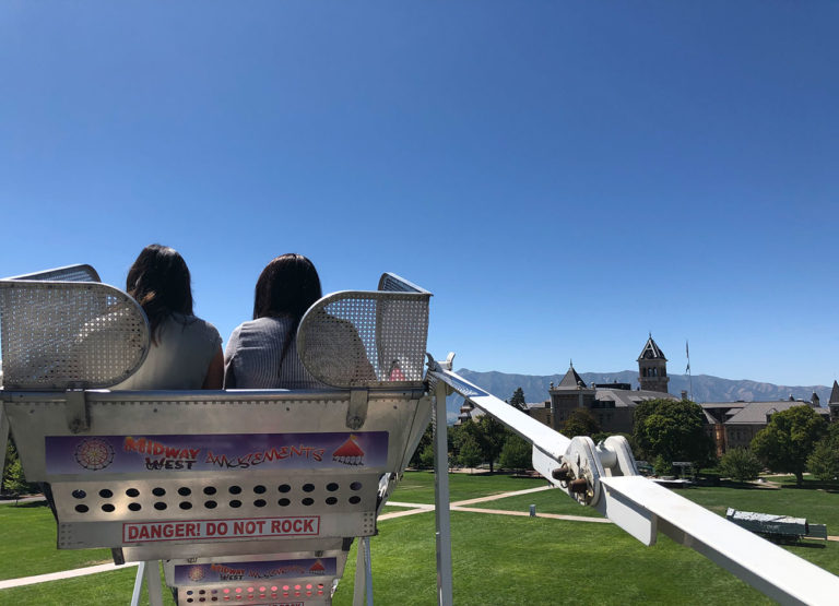 students sit in a ferris wheel overlooking the USU Quad