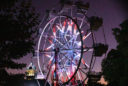 a ferris wheel glows red and blue in the night sky over the USU Quad