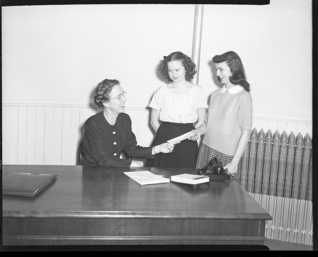 Ione Bennion looks up at two female students with a smile