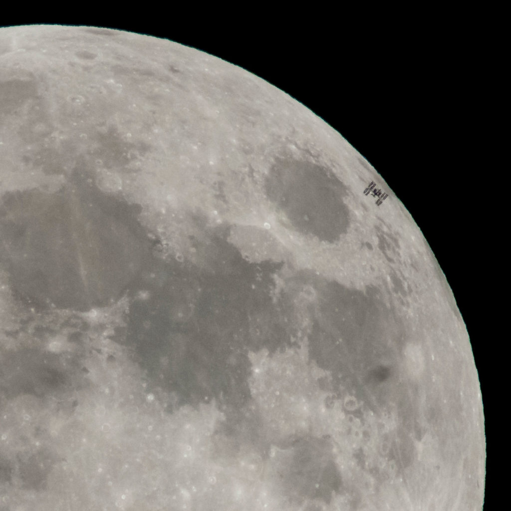 a darkened outline of the ISS as it travels across the glowing moon.