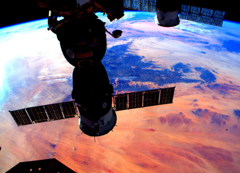 the international space station photographed in shadows while the colorful Earth is in the background glowing orange and purple and blue