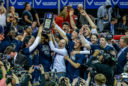USU Aggies men's basketball team celebrates their win by holding up the trophy and raising their hands