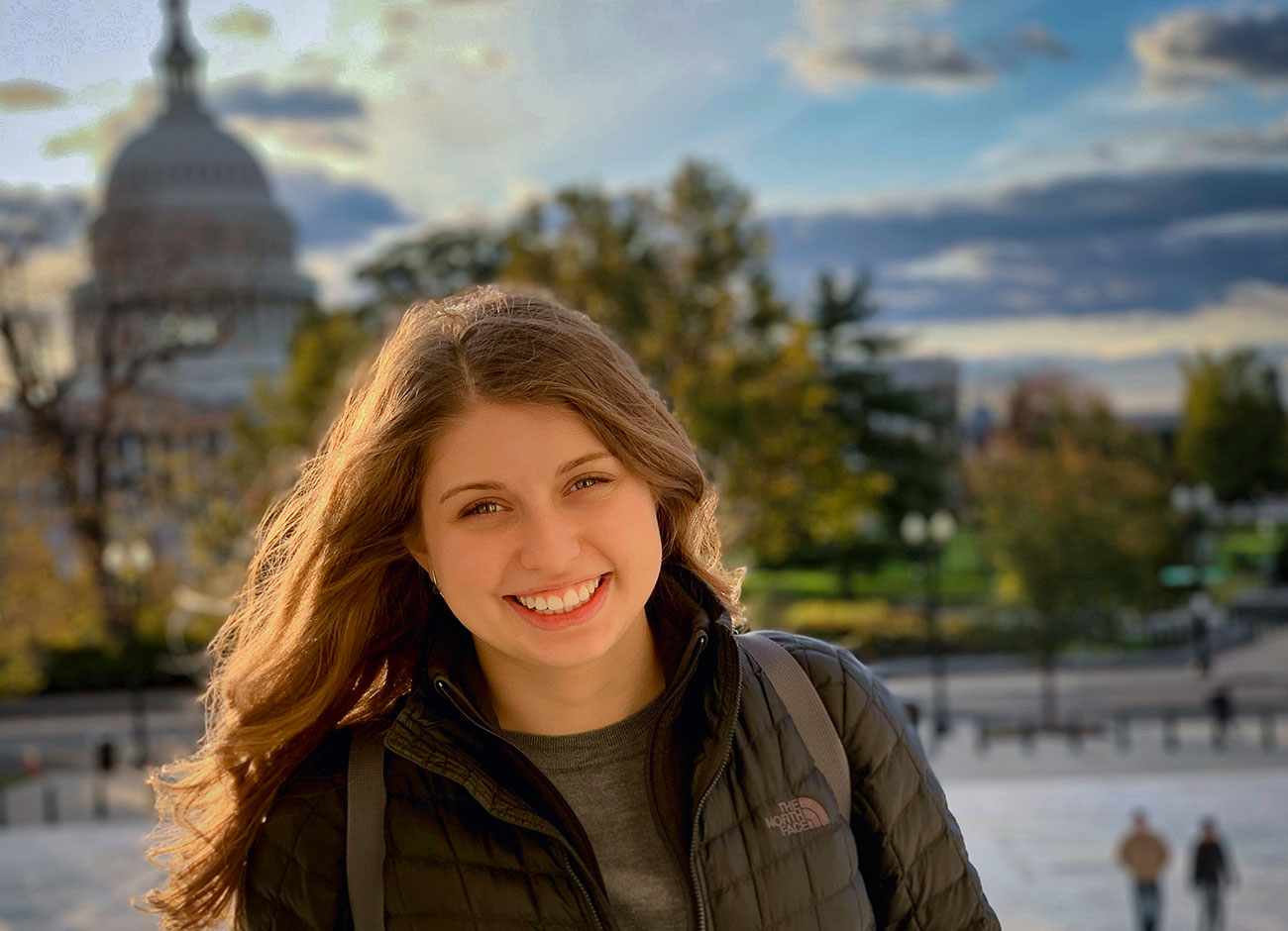 a young woman smiles while standing in front of the U.S. capitol building