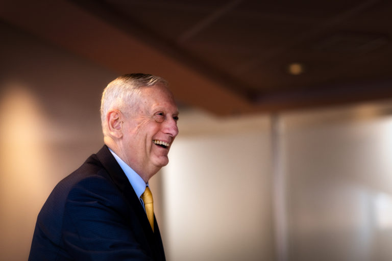 Jim Mattis smiles. He is wearing a suit and yellow tie.