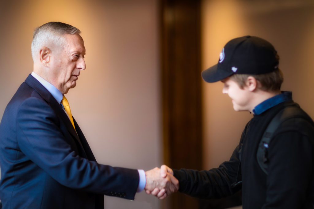 Jim Mattis shakes the hand of a student protester.