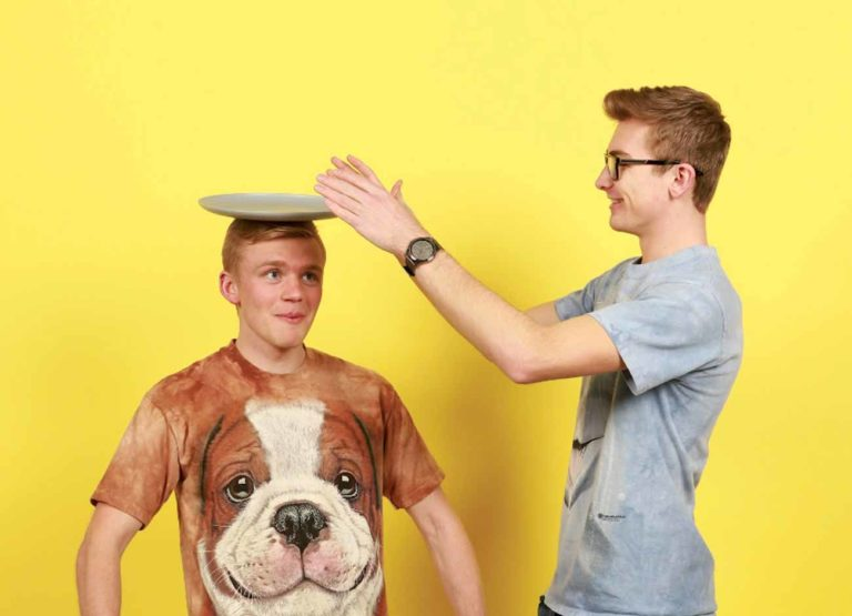 a young man balances a plate on the head of his friend