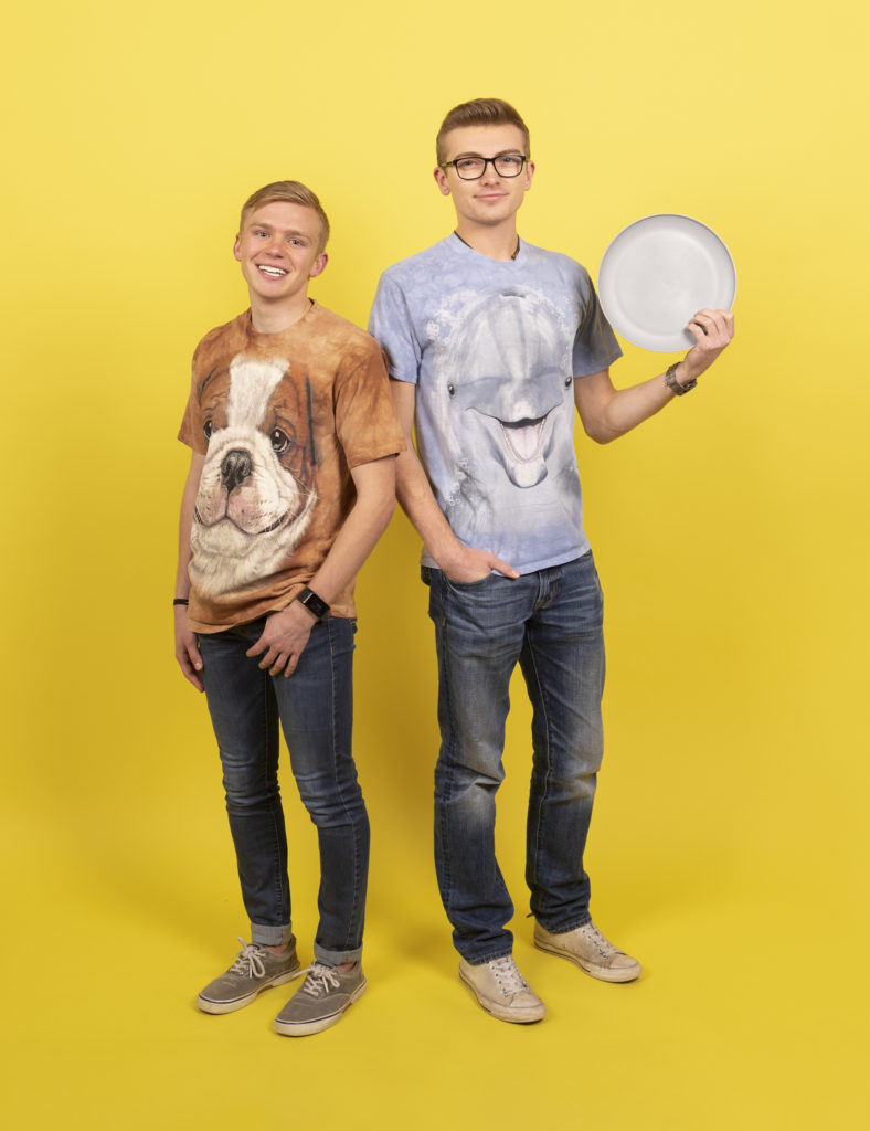 two young men stand back to back holding a dinner plate