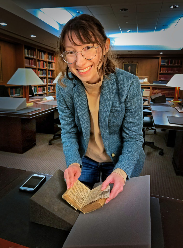 a smiling woman holding open an old book