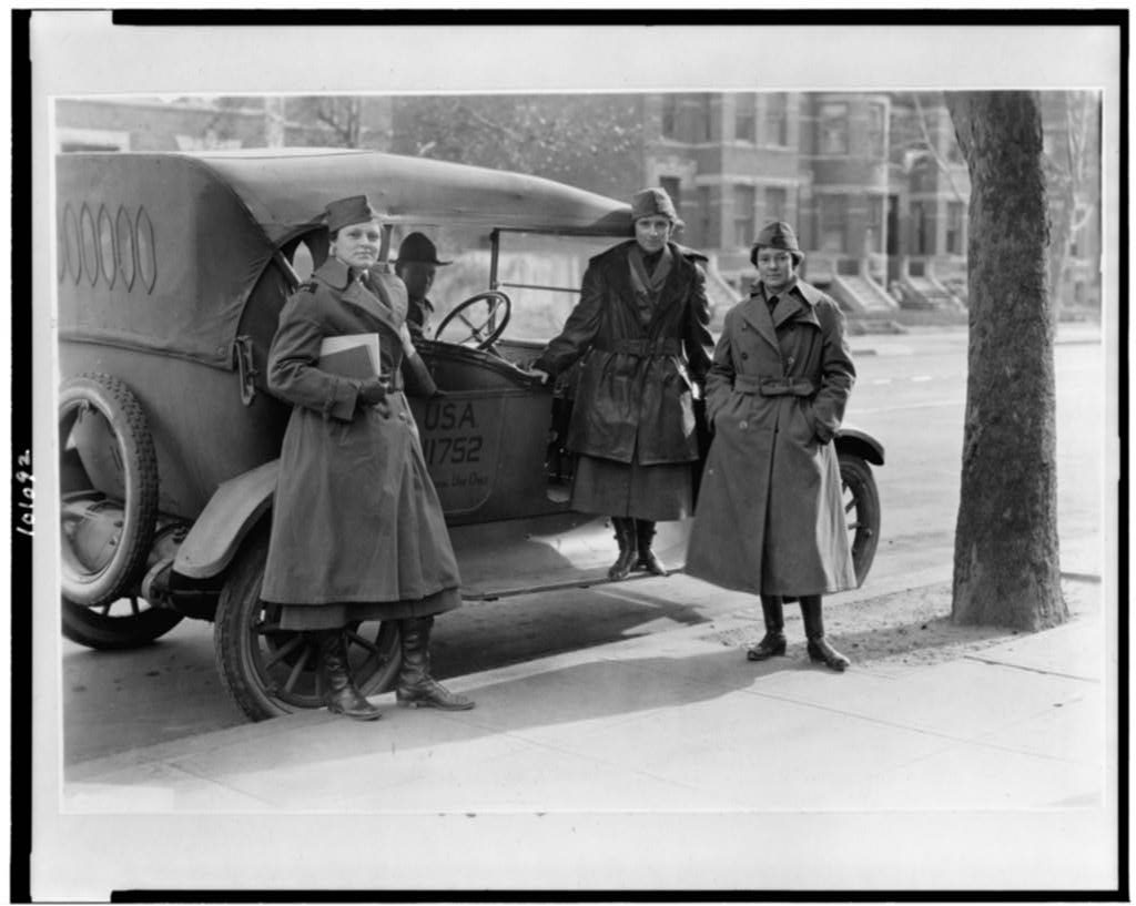 three members of the women's Radio Corp pose beside an Army car.