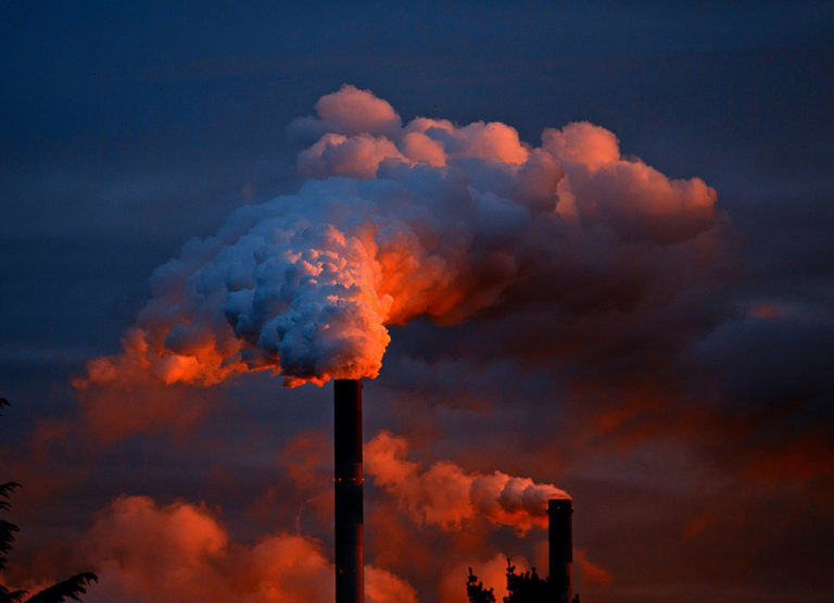 Smoke billows out of a factory at sunset.