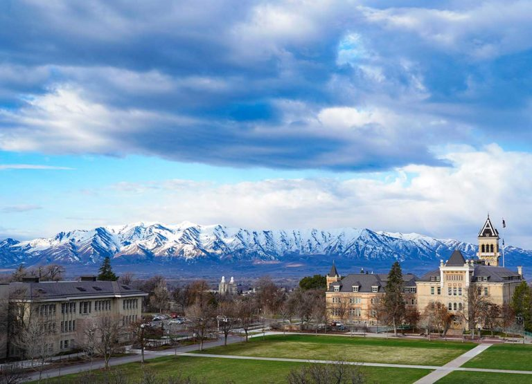 snow-capped mountains flank an empty campus quad.