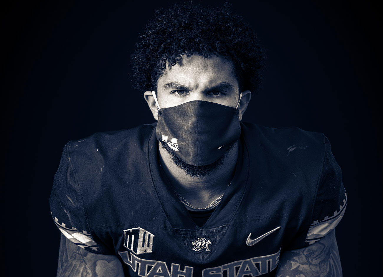 a college football player sits wearing a mask due to covid-19