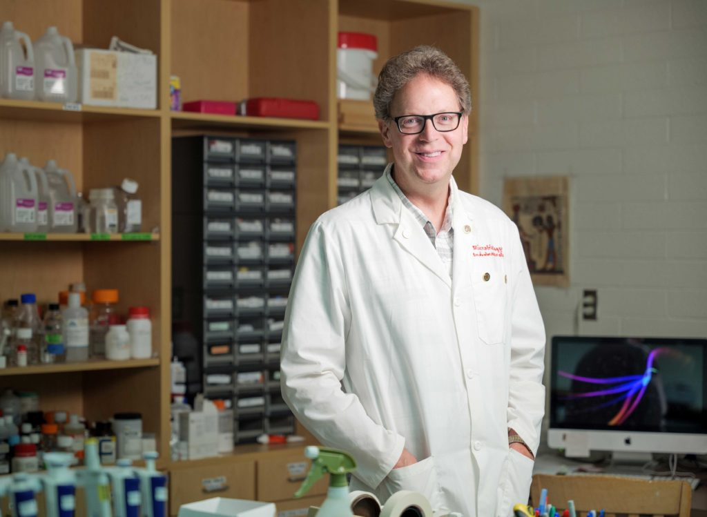 A virologist in a white lab coat stands in the lab where he investigates solutions for COVID-19 and other viruses like it.