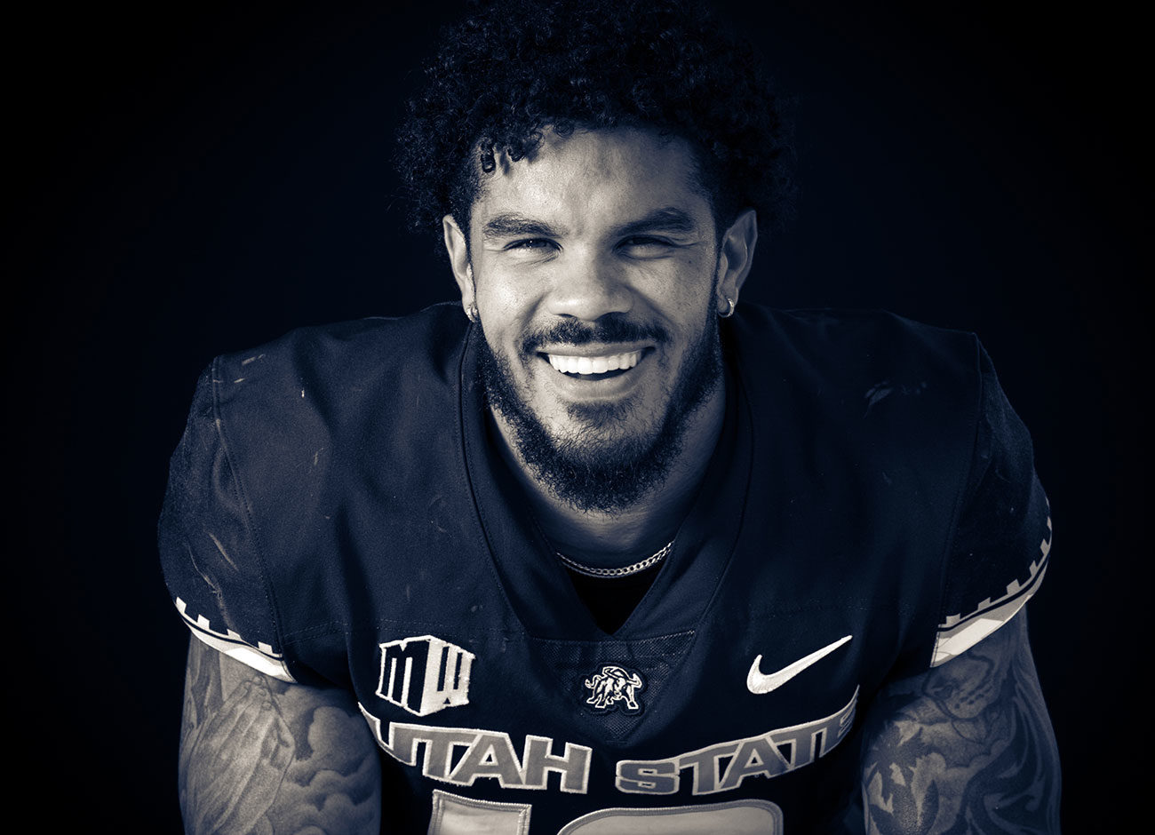 a smiling football player without his helmet
