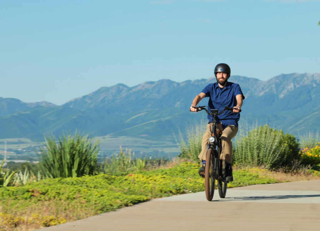 a man rides a bike along a boulevard in Utah. Green mountains are in the background.