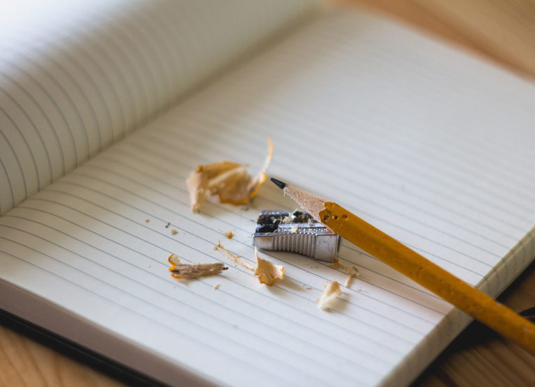pencil, pencil sharpener and shavings, sit on a blank notebook